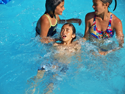 Die Kinder einer Familie bei einem Schwimmkurs