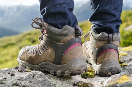 Ein Wanderer mit festen Schuhen auf der Spitze eines Berges
