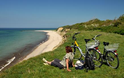 Fahrradfahrerin mach eine Pause an der Ostseeküste